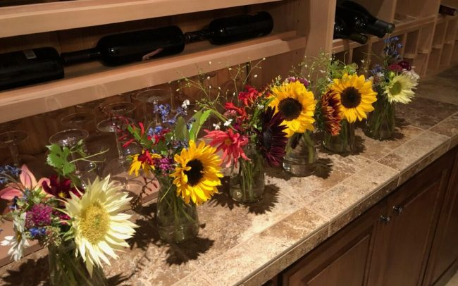 Bouquets of sunflowers and other flowers in vases lined up next to wine glasses and bottles